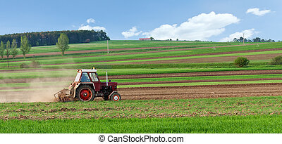 Small tractor harrow on the spring field