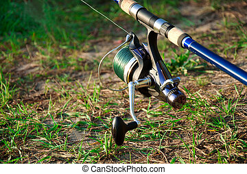 blue fishing reel on the green grass outside