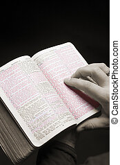 red letters Bible with colors desaturated - hands of a man...