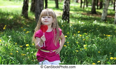 Girl licking a sweet lollipop - Little girl in the park