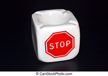 Ashtray in black background Say stop to tobacco