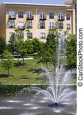 Luxury apartment condo building with fountain in green...