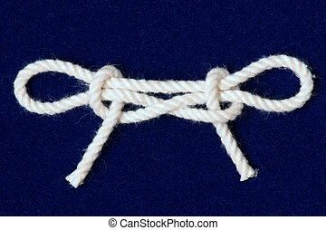 Nautical knot tied in white cord on blue background