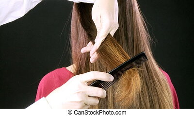 Closeup of scissors cutting hair - Hairdresser cutting long...