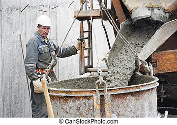 Builder worker pouring concrete into barrel - Builder worker...