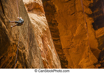 Man rappelling down cliff in desert - Man rappelling down...