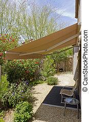 Awning Retracted over Doorway - Arizona backyard with...