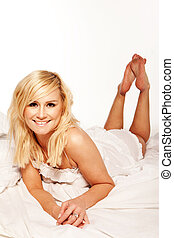 Pretty blonde streched out on her bed with a smile