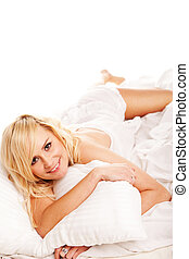 Pretty blonde hugging her pillow in the morning