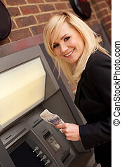 Woman drawing cash at an ATM - Beautiful smiling blonde...