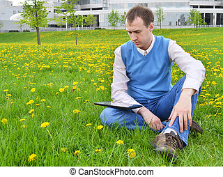 Businessman at the park with tablet.