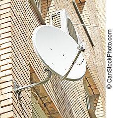 Satellite dish mounted on a brick wall