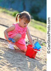 Girl playing alone in the sandpit - Girl playing in the...