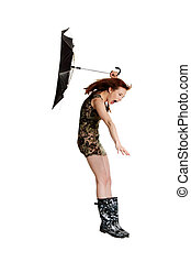 Young woman with umbrella blown by wind.