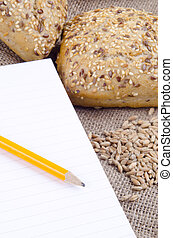 multigrain roll and a booklet for notes
