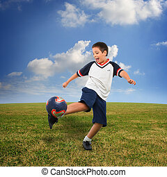 Kid playing soccer outside - Sports. Boy playing soccer...