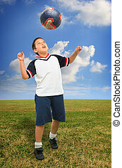 Kid playing soccer outside - Sports Boy playing soccer ball...