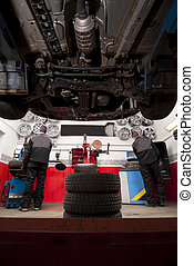 tire repairer - View from under a car in a tire shop