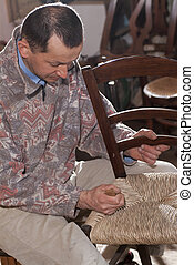 Carpenter weaves straw for repair of old chairs