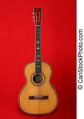 Guitar over red background. Beautiful musical instrument