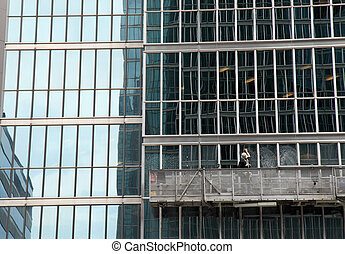 window washer cleaning windows on a modern highrise office