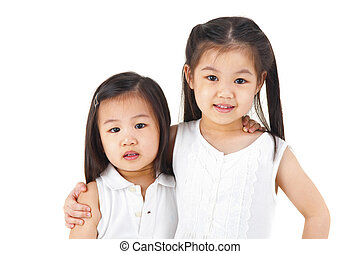 Asian sisters arms around on plain background