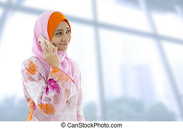 On the phone. - Muslim business woman on the phone, looking...