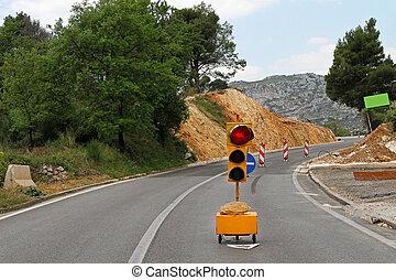 Road works - Red traffic light at road after mudslide
