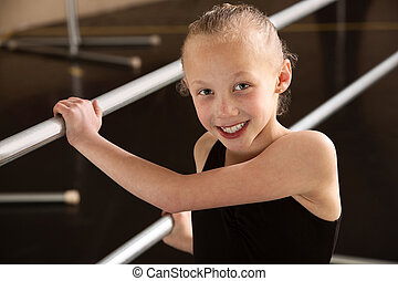 Child Ballerina - Smiling ballerina girl holding balance...