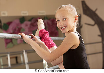 Child Ballerina Stretching Her Leg - Little ballerina girl...