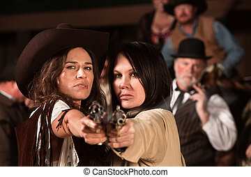Pretty Gunfighters - Two pretty cowgirls point revolvers at...