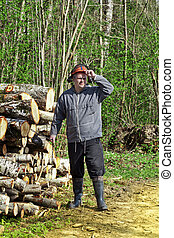 Lumberjack near a pile of logs