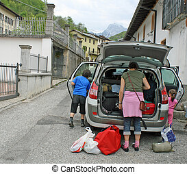 Family car ready to go with the trunk full of suitcases and...