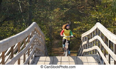 girl goes by bicycle on a bridge