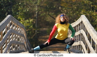 woman doing stretching exercise on a bridge