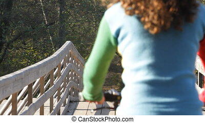 Beautiful girl goes by bicycle on a bridge