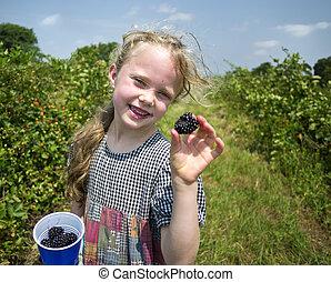 Little girl holding big blackberry. She has some blackberry...