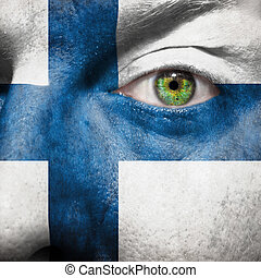 Flag painted on face with green eye to show Finland support