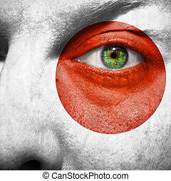Flag painted on face with green eye to show japan support