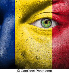 Flag painted on face with green eye to show romania support