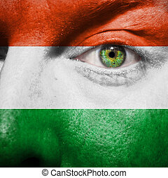Flag painted on face with green eye to show hungary support