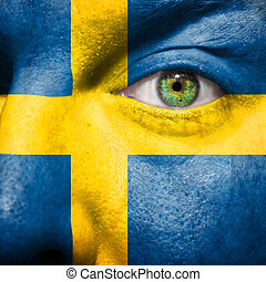 Flag painted on face with green eye to show sweden  support