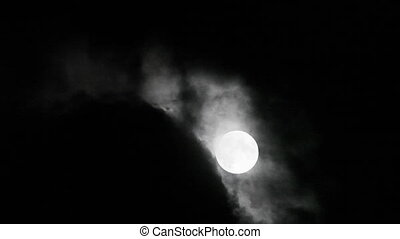 Super moon moving in and out clouds