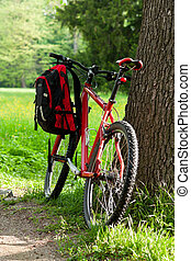 Bike and backpack among the green of nature in spring