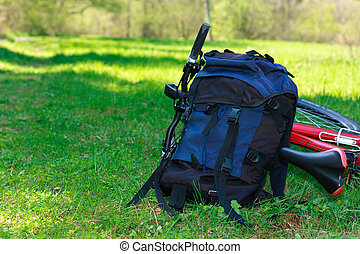 Backpack and Bike Lying on Green Grass