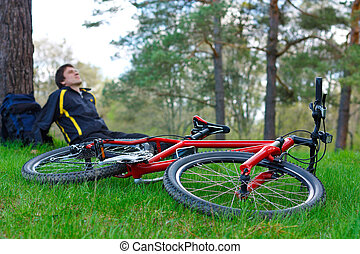 Red bike lying on green grass. Cyclist relaxes under the tree in the background against the background of green nature