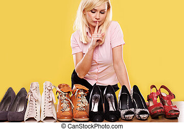 Blonde lady with a passion for shoes looking at part of her...