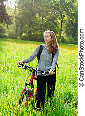 Happy woman cyclist with bike among the green nature