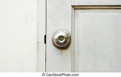 Silver door handle on white old door background