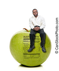 Man Sitting on Green Apple with Nutrition Label